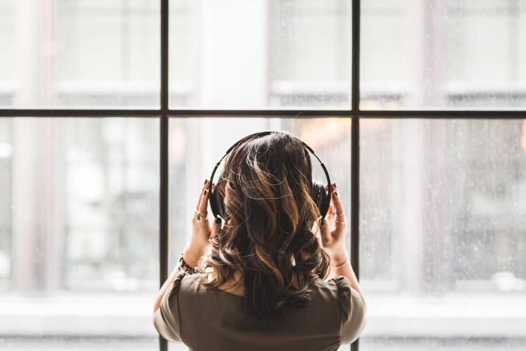 girl in noise cancelling headphones avoids noisy environment