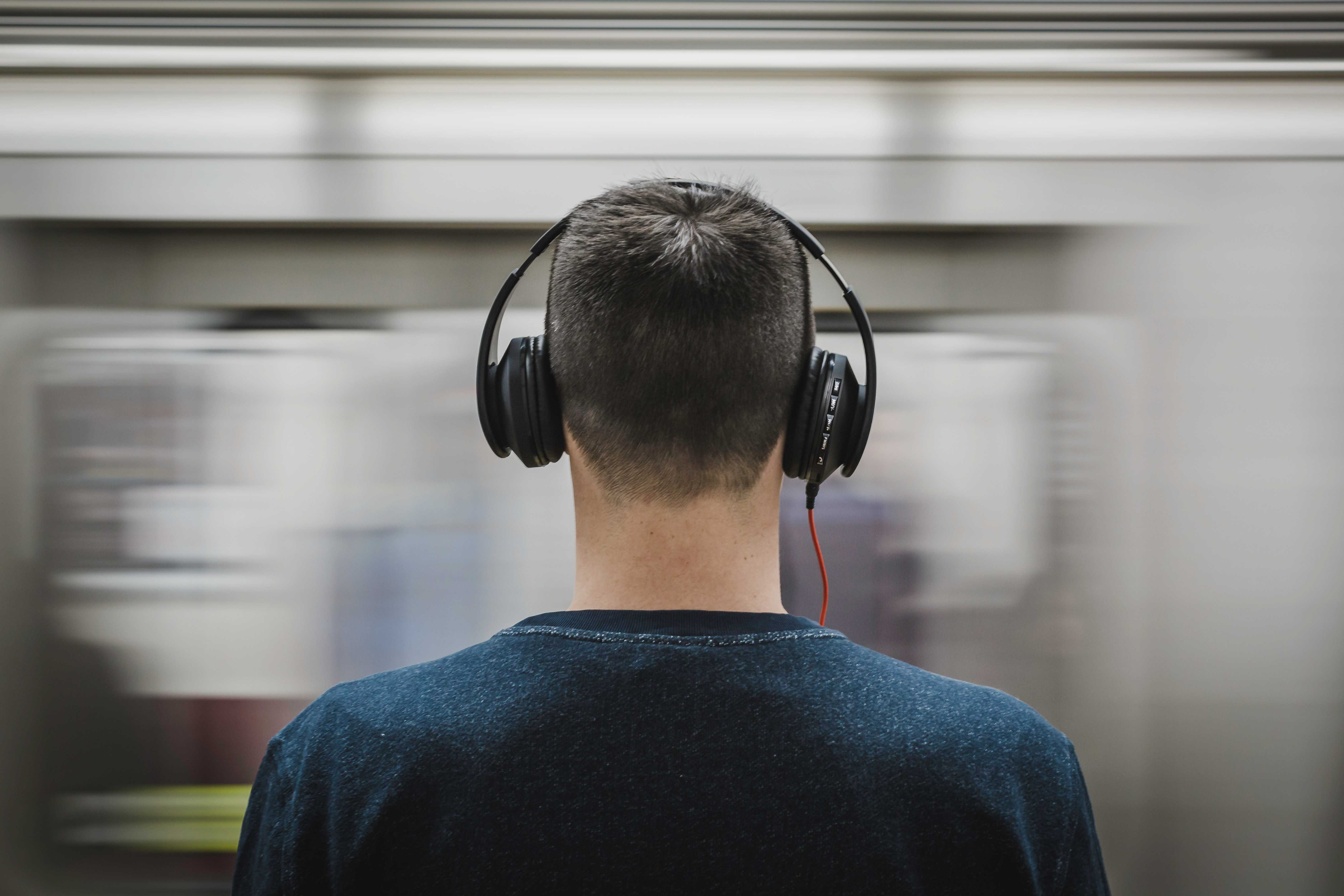 Man with noise cancelling headphones in metro station
