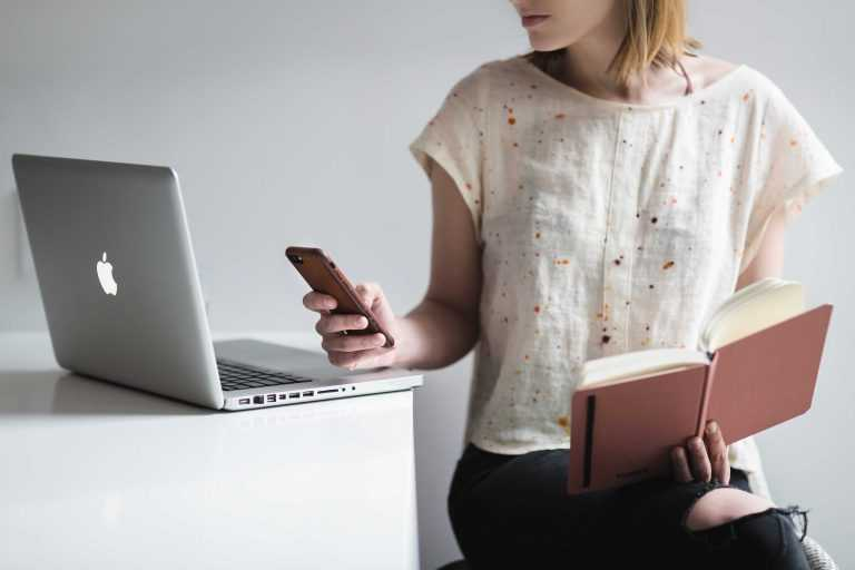 woman multitasking with phone, book and Mac
